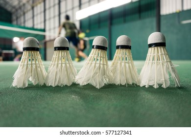 White badminton ball on green floor with blurred player in badminton court