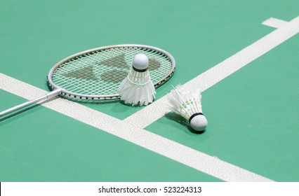 White badminton shuttlecock on a green floor with blurred players in badminton court