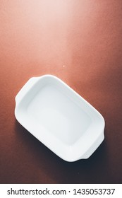 White baking dish Empty rectangular White baking dish over a brown background, top view