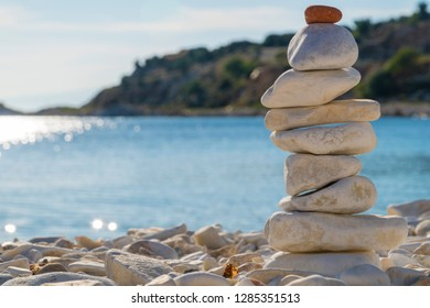 white balanced and stacked strones at the beach in sunny day and in front of sea.
