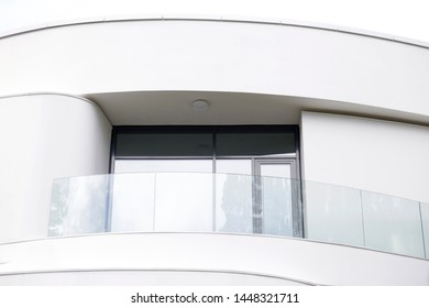 White balcony with transparent glass balustrade on a top floor. Close-up photo of modern residential building exterior. Abstract contemporary architecture fragment.