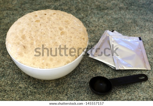 A white ball with active yeast in warm water beside a black measuring spoon and sachet.