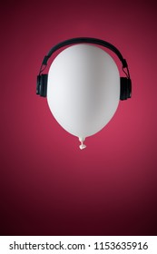 white balloon headphones on red backraund fly