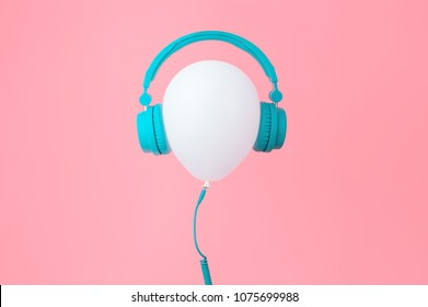 White balloon with tiffany color headphones on Pink background. Contemporary design. Trendy colors.