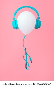 White balloon with tiffany color headphones on Pink background. Contemporary design. Trendy colors. Vertical