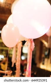White balloons decorated with pink ribbons hang in the hall