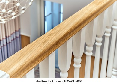 White balustrade. Balcony wooden railing with white balusters in a bright large room