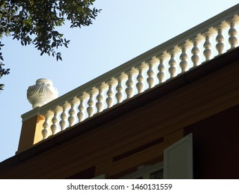 A white banister is on the top of a building. Close to the banister is located a classic vase. The building is cold Villa Durazzo in Liguria, in Italy.