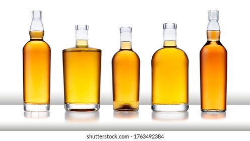 A white bar with a row of bottles full of golden whisky, with no label or branding, isolated on white with a slight reflection