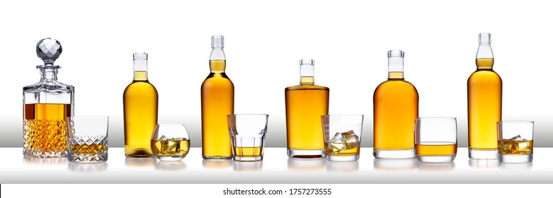 A white bar with a row of bottles of golden whisky, with no label or branding, and glasses of whisky and ice, isolated on white with a slight reflection