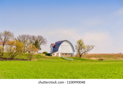 White barn and green pasture on farm in rural western Wisconsin in Spring.