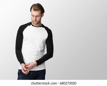 White baseball t-shirt with black long sleeves on a young man in jeans, isolated with copy space, mockup.