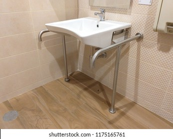 White basin and stainless handle bars or rails in a toilet for disabled people or elderly people