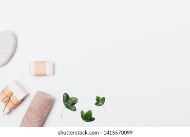 White bath background of soap, terry towel, pumice and green leaves, flat lay composition with copy space.