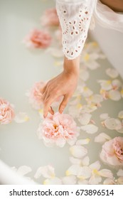 White bath with milk and rose petals. Relaxation and harmony