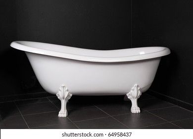White bath on a black background in a black bathroom