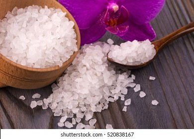White bath salt in a wooden bowl with a spoon and an orchid on wooden table