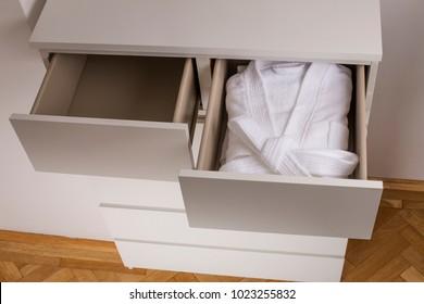 White bathrobe inside an open drawer cabinet