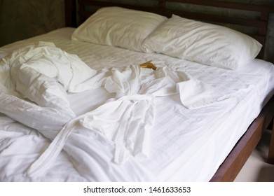White Bathrobe on bed in comfortable bedroom after wake up with messy bedding sheets and duvet with wrinkle messy in hotel room
