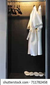 White Bathrobe on clothes hanger and slippers in wardrobe