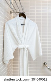 White bathrobe on hanger with mosaic tiles background