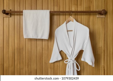 White bathrobe with towel on hanger with wooden wall