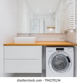White bathroom with countertop basin, big mirror and washer