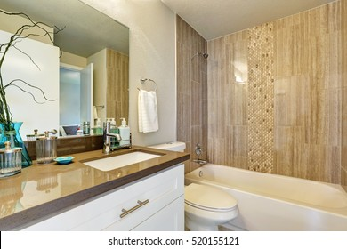 White bathroom with gray and brown tile wall trim. Northwest, USA