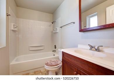 White bathroom with mahogany vanity cabinet, tub and shower combination. Northwest, USA