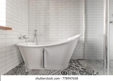 White bathroom on a tiled wall background Classic bathtub
