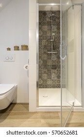 White bathroom with shower, toilet and wood effect flooring