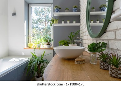 White bathroom with window and green plants. Cozy interior with wooden counter, brick wall, ceramic sink and modern design. Jungle in a bathroom.