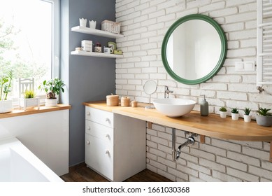 White bathroom with window, wooden counter and design washbasin. White bricky wall with round mirror. Interior in loft apartment.
