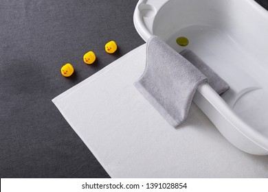 White bathtub and bath mat on a gray background, grey towel on the side