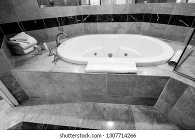 White bathtub and brass taps decorated with marble tiles