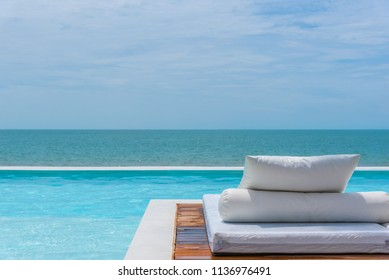 White beach bed at outdoor swimming pool seaside turquoise sea or ocean with horizon of blue sky at resort or hotel when vacation travel for relax