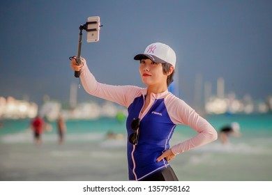WHITE BEACH, BORACAY ISLAND, PHILIPPINES FEBRUARY 7 2019: Young chinese girl in swim suit taking selfie on her mobile smart phone on the beach