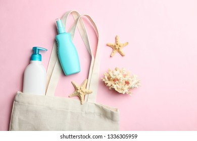 White beach eco bag, plastic bottles with sunscreen and sea decorations on pink background. Concept summer vacation. Top view, copy space.