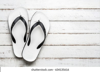 White Beach flip flop on white wooden floor