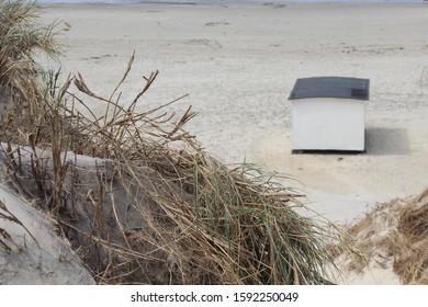 White beach house seen from sand dune