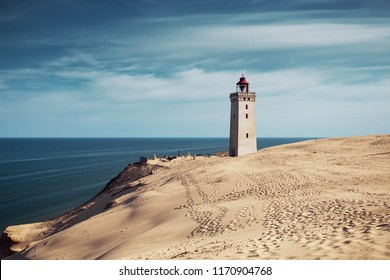 White beach sand dunes at the north danish coastline in summer sun light and blue sky. Rubjerg Knude Lighthouse, Lønstrup in North Jutland in Denmark, Skagerrak, North Sea