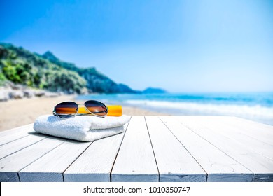 White beach towel with sunglasses on white wooden table. Free space for your decoration of product or text. Blurred landscape of sea and green trees with blue sky.