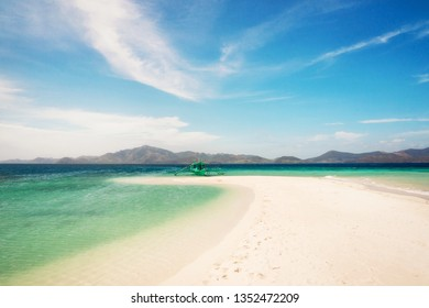 White beach with traditional philippine bangka boat, turquoise water and sandbar, Bulog island, Philippines.