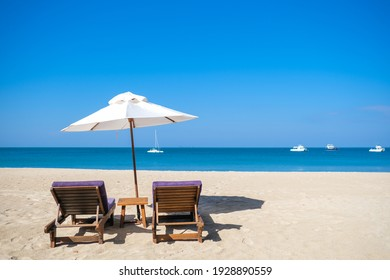 White beach umbrella on the beach against the blue sky and blue sea background on sunny day. Summer vacation and holiday concept.