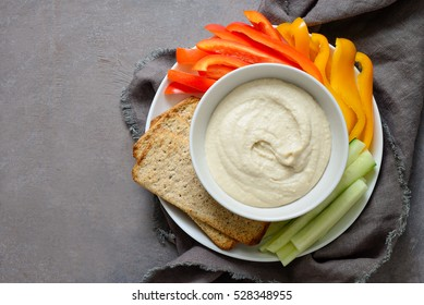 White bean hummus served in a bowl with fresh vegetable sticks and whole grain crackers, view from above, space for a text