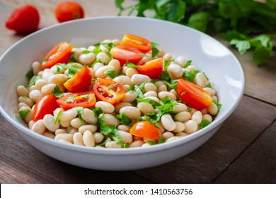 White bean salad with cherry tomatoes and parsley in bowl
