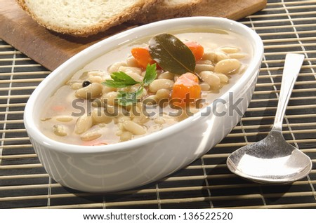 white bean soup with carrots in a white bowl