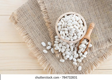 white bean in wood cup on sack background