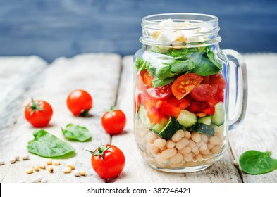White beans cucumber tomato red pepper feta spinach salad in a jar. toning. selective focus