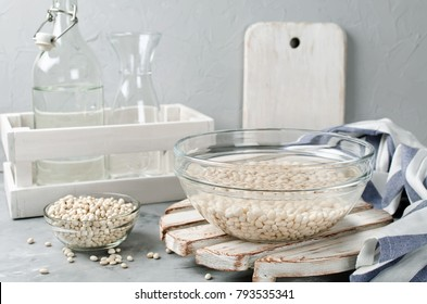 White beans soaked in water in a glass bowl. Ingredients for cooking